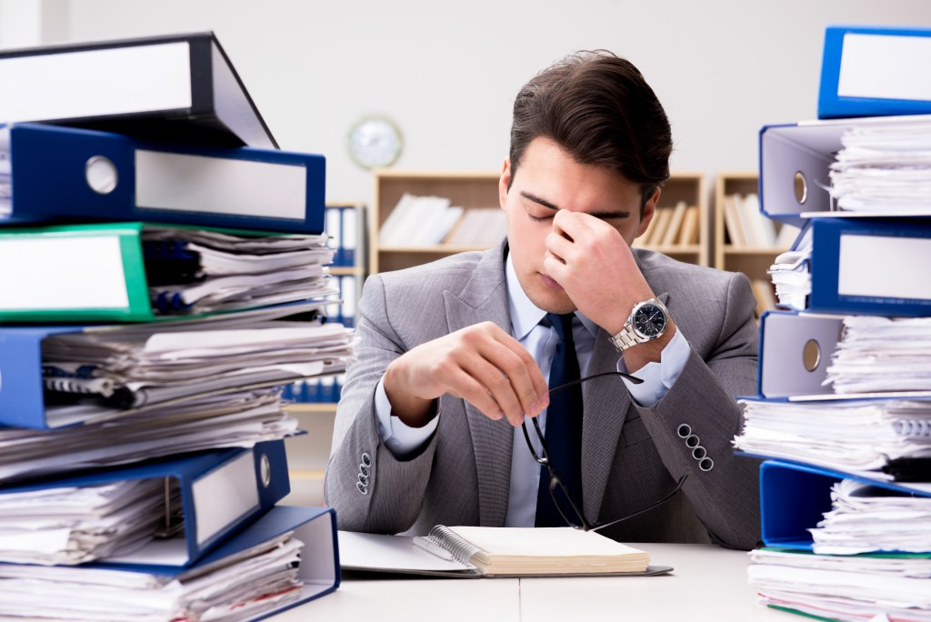 Stressed employee with a lot of paper work on his desk