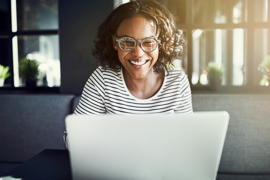 Female smiling while working in her laptop