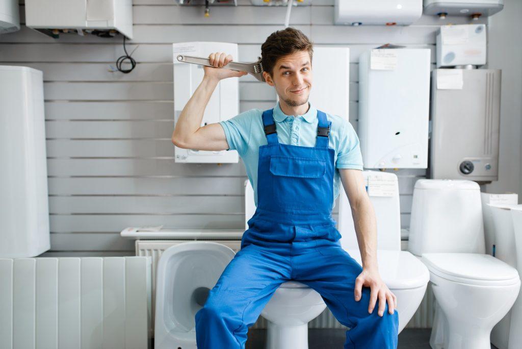 Plumber sitting on toilet in plumbering store