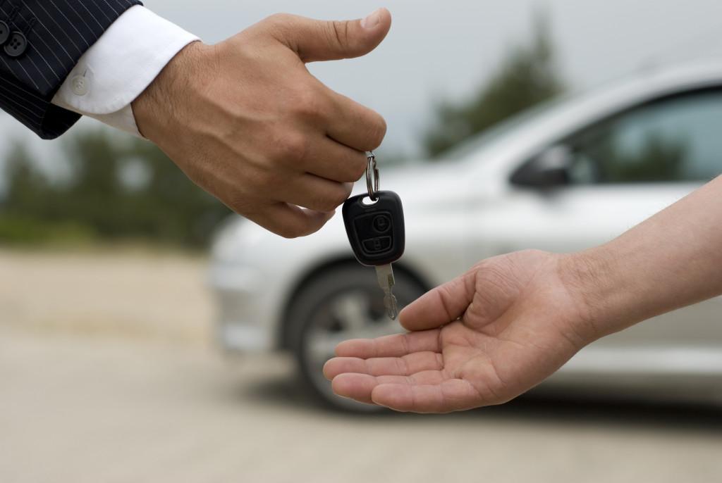 car salesman handing the car key to a customer