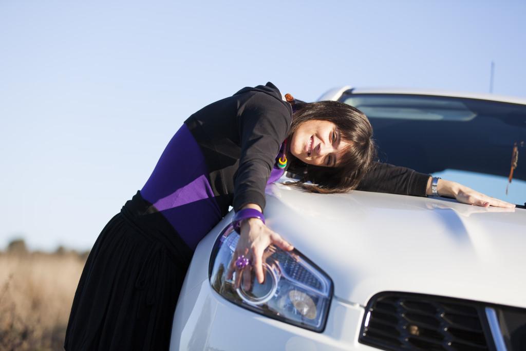 Beautiful woman embracing her new car
