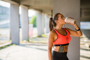 woman drinking water after doing workout