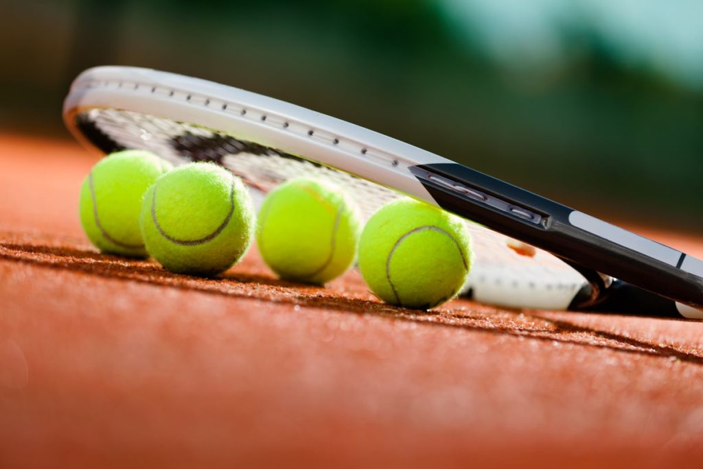 tennis racket and tennis balls on the ground