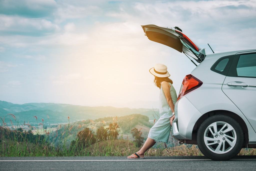 Woman by the road with car