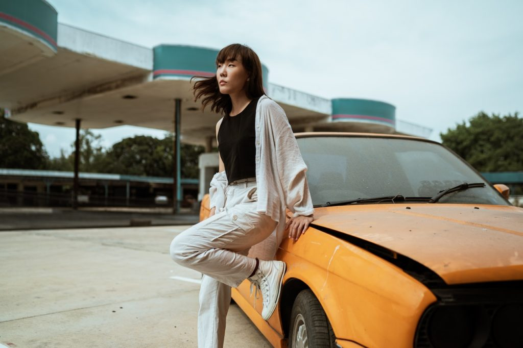woman leaning on her car