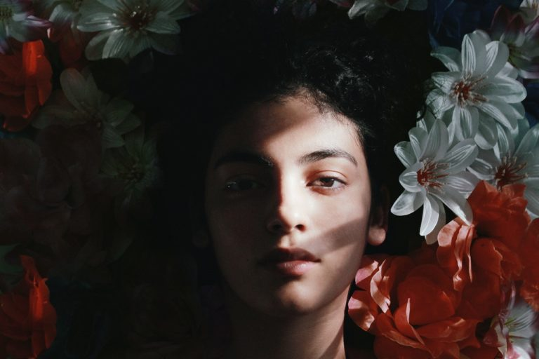 woman's face on a bed of flowers