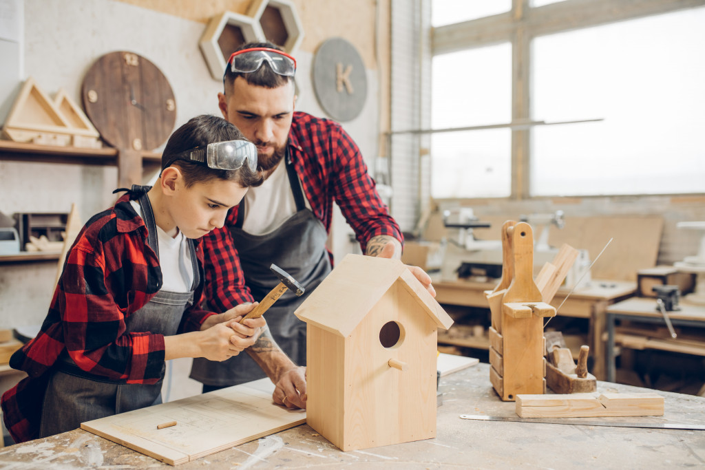father and child building a bird house