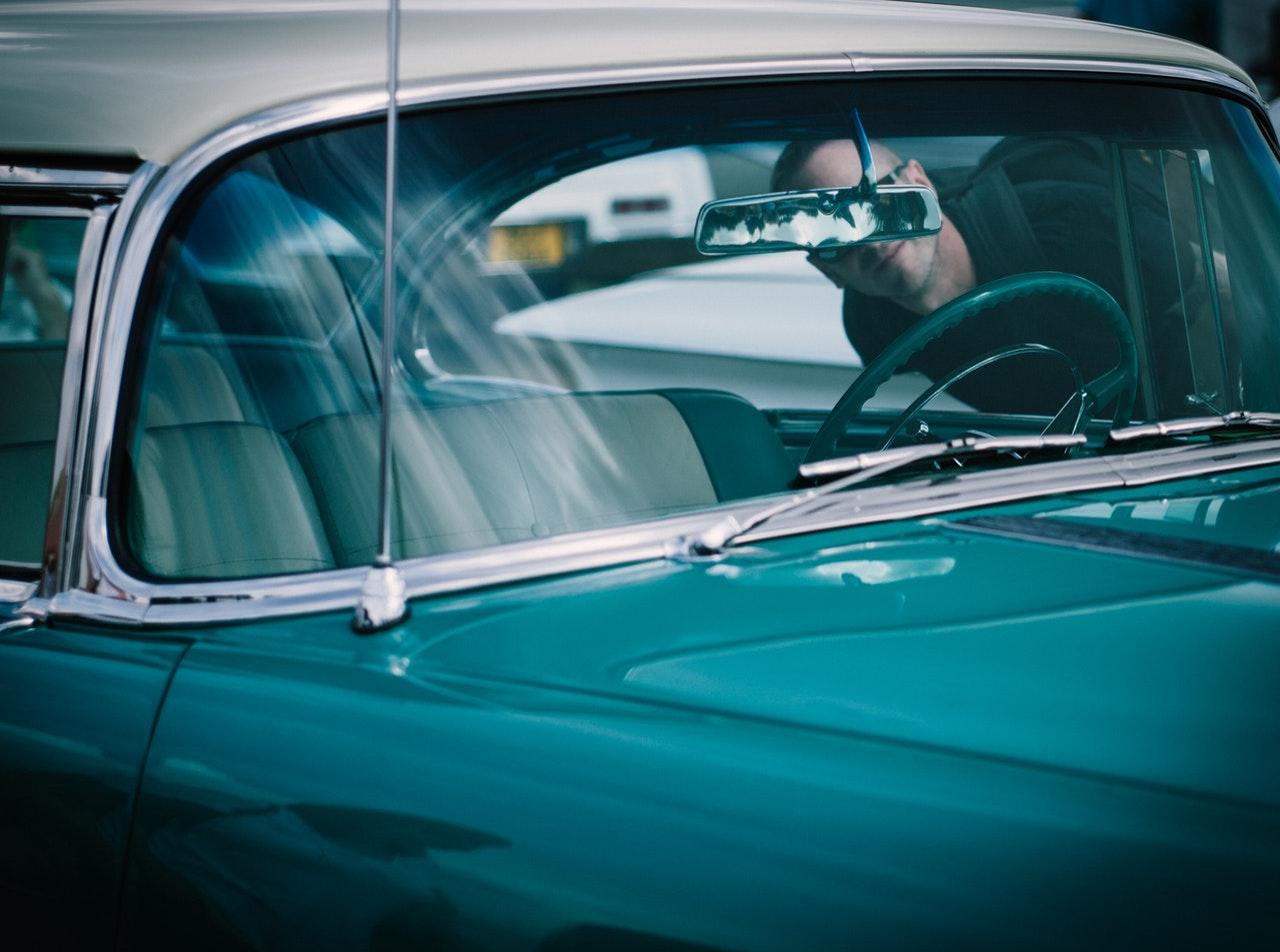 man inspecting a car
