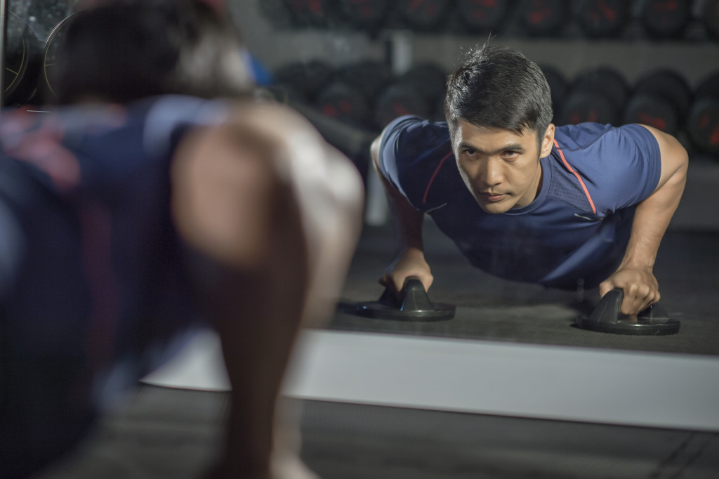 man doing push ups at the gym