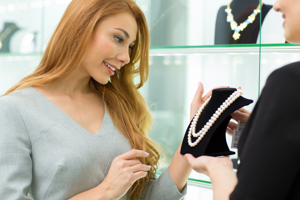 woman looking at a necklace